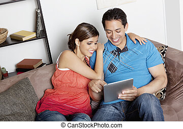 At Home - Couple snuggling at home on the sofa reading a...