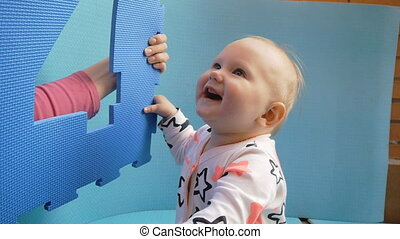 Baby and mother plays with eva puzzle mat