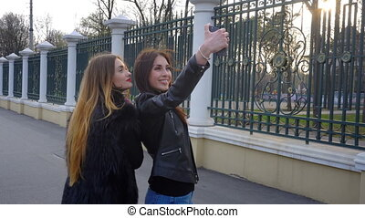 two charming girls make selfi in Park - two charming happy...