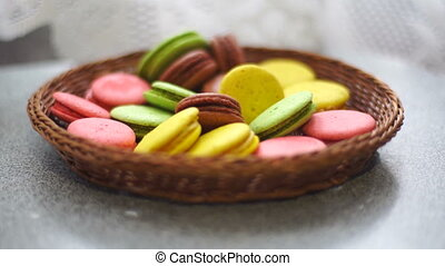 French macaroon cookies in the wicker plate on a table