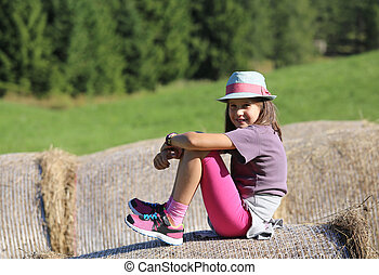 Nice little girl with long hair over hay bale in the...