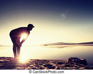 Deep breathing runner silhouette bended with hands on knees....