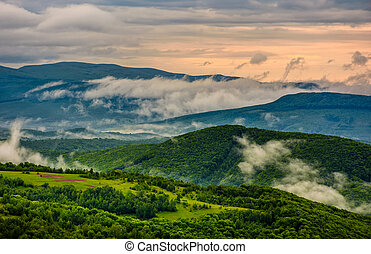 foggy mountain ridge over the rural fields in springtime -...