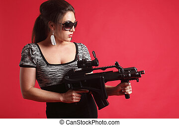 Sexy woman with gun - Young and sexy woman with an assault...