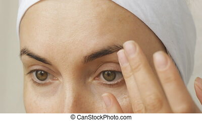 Young woman taking care of her face skin at home. Closeup...
