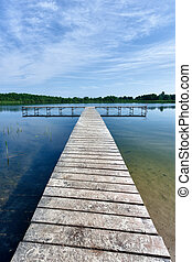 pontoon - Wooden pontoon on a lake with forest opposite and...