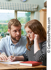 Male Home Tutor Helping Girl Struggling With Studies