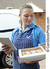 Baker With Digital Tablet Making Home Delivery Of Cupcakes