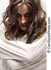 Young insane woman with straitjacket looking at camera...