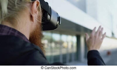 Closeup back view of young bearded man using virtual reality headset for 360 VR experience outdoors