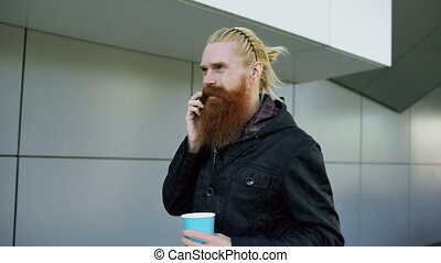 Dolly shot of happy beard young man talking on the smartphone and drinking coffee while walking in the street