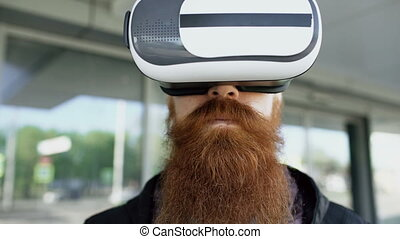 Closeup of Young bearded man using virtual reality headset for 360 VR experience and take of glasses smiling outdoors