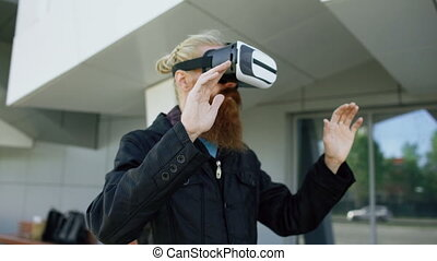 Dolly shot of Young bearded man using virtual reality headset for 360 VR experience and take of glasses smiling outdoors