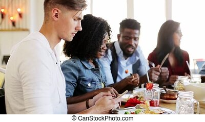 couple with friends and smartphones at restaurant -...