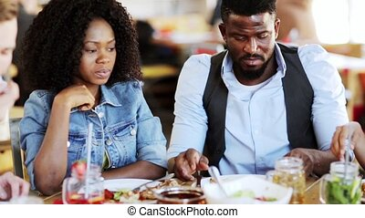 african american couple eating food at restaurant - leisure,...