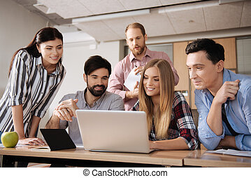 Group of friendly colleagues while working together - It is...