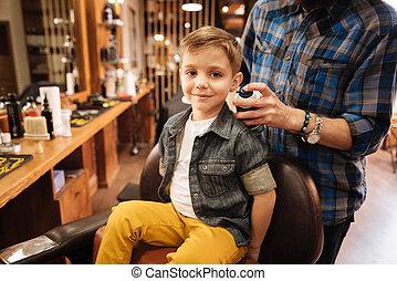 Happy nice boy being in the barbershop