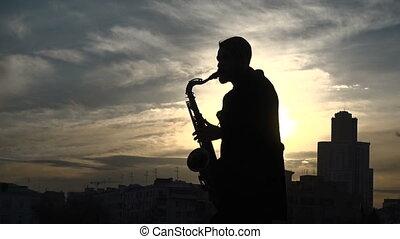 Street musician play saxophone sunset silhouette - A street...