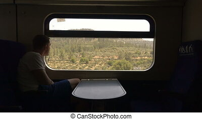 Sad man in headphones looking out window train