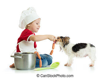 Role-playing game. Kid boy plays chef with pet. Child weared...