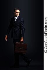 Portrait of a business man  with briefcase isolated on black bac