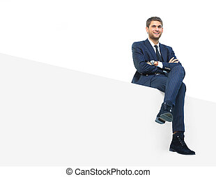 Happy businessman sitting on a banner - handsome young...