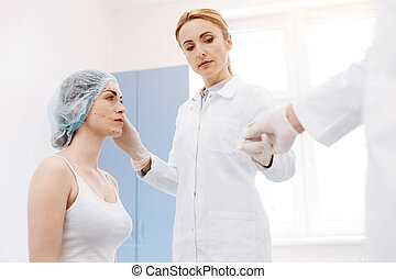 Serious female surgeon performing an operation
