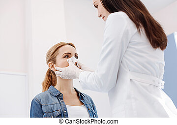 Pleasant female patient reshaping the form of her nose