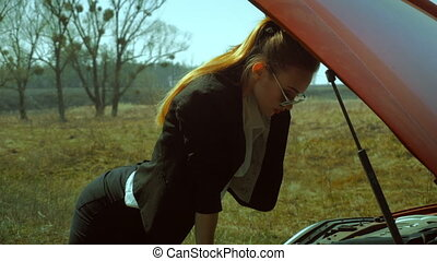 hot girl looks under the hood of the car - hot blonde girl...