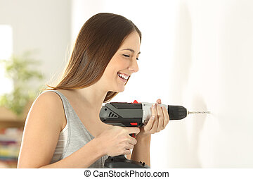 Girl using a drill in a wall at home