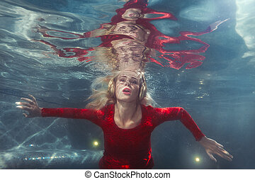 Woman listens to music underwater. - Woman listens to music...