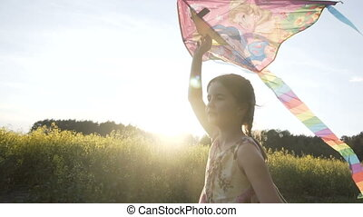 Cute Girl Plays with Kite - Sunset shot of cute teenager...
