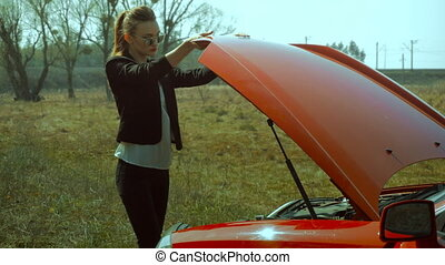 cute girl closes the hood of the car - cute girl closes the...