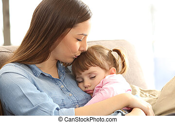 Mother kissing to her baby daughter - Close up portrait of a...