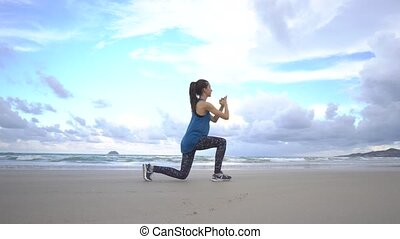 Young woman training on the beach in front of sea. Lunges. Morning gymnastic exercises. Healthy active lifestyle concept.