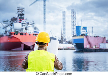Shipbuilding engineer checking documents at the dockside in...