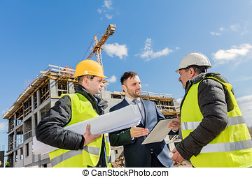 Engineers and investor meeting at the construction site.