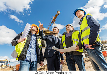 Engineers and investor meeting at the construction site. -...