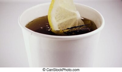 Slow motion. In a cardboard glass with tea falls a lemon