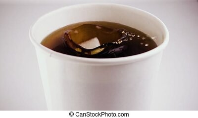 Slow mo. In a glass of tea drops a cube of sugar - Slow mo....