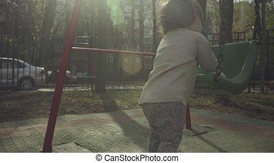A kid near a swing in the courtyard. 4K