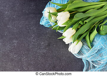 A bouquet of white fresh tulips on a blue abstract texture background. Love and wedding concept. Romance.