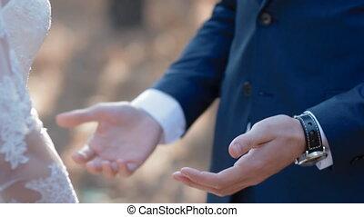Groom kiss hands of his bride