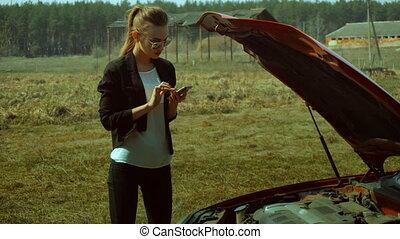 blonde calls a mechanic near the broken car in the field