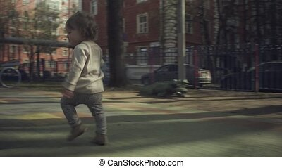 A kid running in the courtyard - Rear view of a kid running...