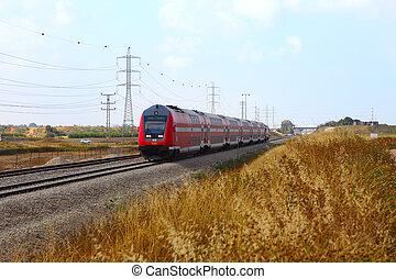 red passenger train passes over the field - NETANYA, ISRAEL-...