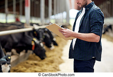 farmer with clipboard and cows in cowshed on farm -...