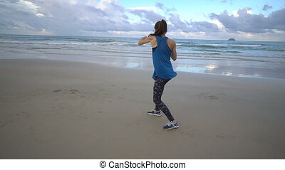 Female boxer shadow boxing on sea shore beach on sunset. Attractive female with long brown hair hit with hands, working out, do sports in the evening. Fit sporty