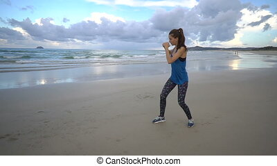 Athlete outline boxing into air on sea shore beach on sunset. Attractive female with long brown hair hit with hands, working out, do sports in the evening. Fit sporty