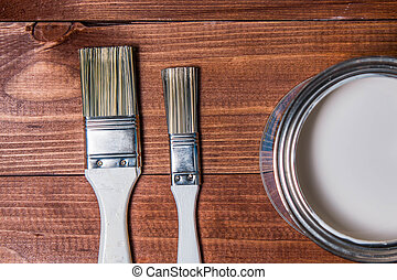 Painting brushes near a metal jar with white paint on an oak table